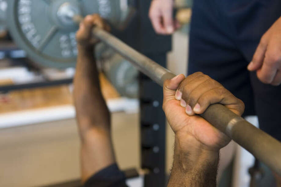 Houston Texans strength and conditioning coach Ray Wright shows the proper technique for bench press in the Texans weight room. Photo: Brett Coomer, Houston Chronicle