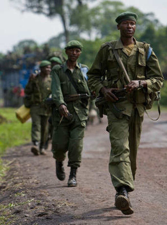Congolese army troops, with former rebel combatants in their ranks, march north through Rumangabo, about 27 miles north of Goma, Congo, Thursday en route to Rutshuru where they will meet Rwandan troops for joint operations. Rwanda has deployed additional battalions to Congo and has around 4,000 troops in the Central African nation as part of an operation both nations say is aimed at disarming Rwandan Hutu militiamen, the U.N. said Thursday. Photo: T.J. KIRKPATRICK, AP