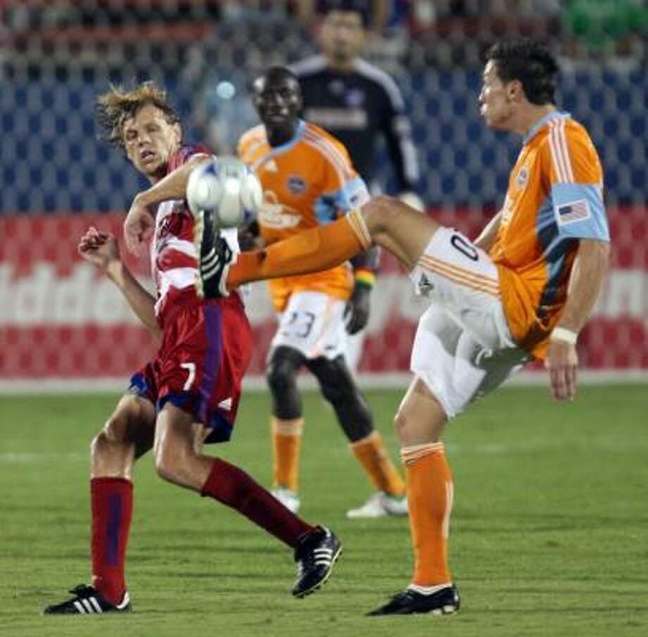FC Dallas' Dave van den Bergh, left, dodges a ball kicked by the Dynamo's Geoff Cameron during the second half of their game Thursday in Frisco. FC Dallas won 1-0 on Jeff Cunningham's 20th-minute goal. Photo: Vernon Bryant, AP