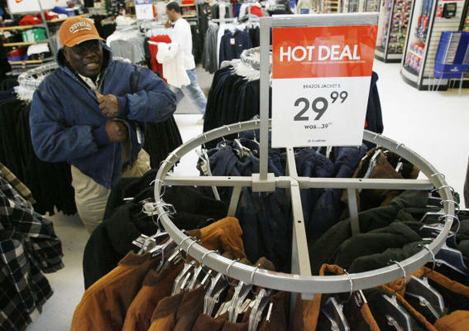 R.B. Williams, of southwest Houston, tries on a jacket marked as a Hot Deal at Academy Sports + Outdoors this week. Consumers are focusing on basics this year. Photo: Julio Cortez, Chronicle