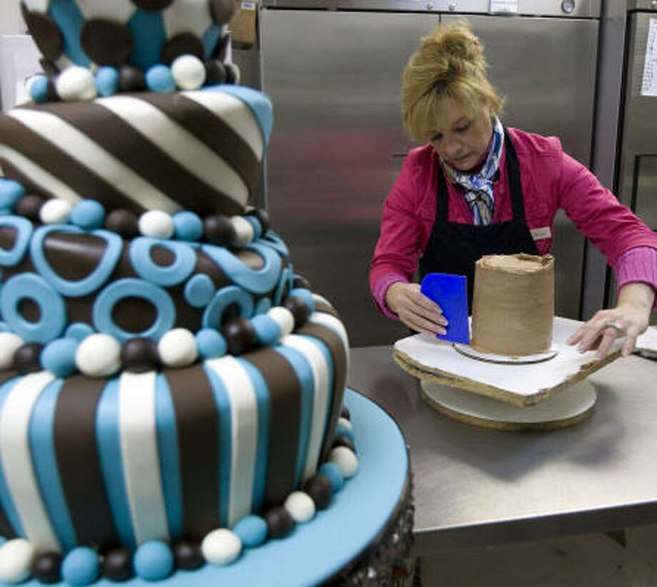 Jessie Lopez works on a wedding cake at a bridal trade show at the George R. Brown Convention Center in Houston earlier this year. The city is considering farming out the business of promoting such events. Photo: Johnny Hanson, Chronicle