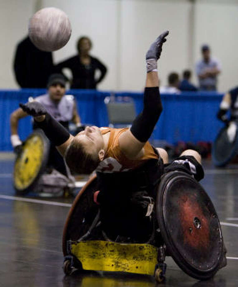 Jace Beck of the Austin-based quad rugby team the Texas Stampede, reaches back for a pass during a game against the San Antonio Roughriders at the U.S. Paralympic Military program sports expo Jan. 17 at the George R. Brown Convention Center. Photo: Eric Kayne, Chronicle