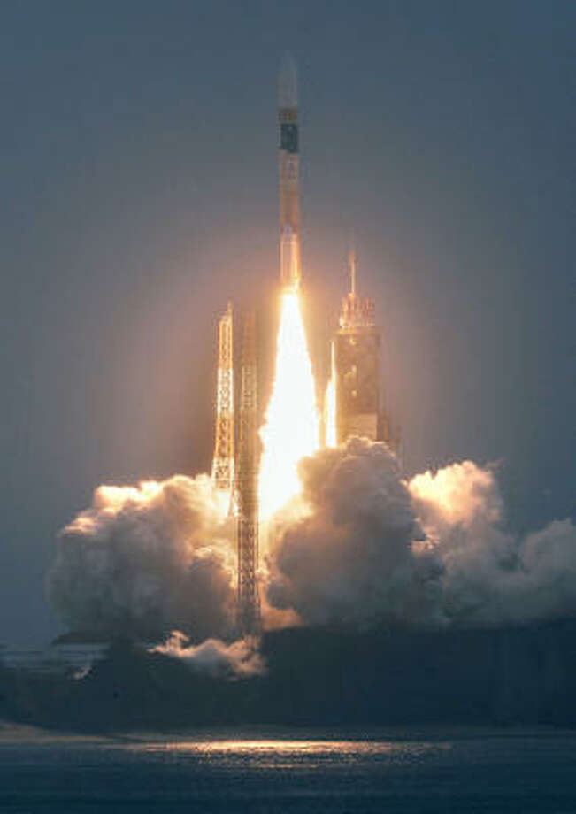 An H2A rocket, carrying the world's first greenhouse-gas monitoring satellite, takes off from the Tanegashima Space Center, southern Japan, today. Photo: Kyodo News, AP