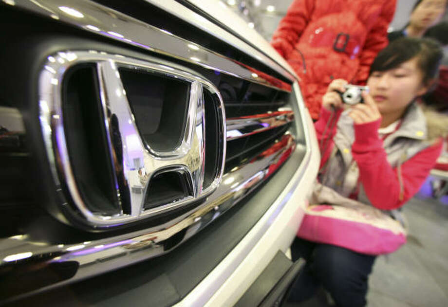A visitor takes a photo of a Honda car displayed at the Honda Motor Co. headquarters in Tokyo today. Japan's No. 2 automaker slashed its annual profit target by over half today. Photo: Itsuo Inouye, AP