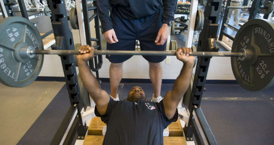 Texans strength and conditioning coach Ray Wright shows the proper technique for bench pressing. Note the presence of a spotter, which is essential, especially when using free weights. Photo: Brett Coomer, Chronicle