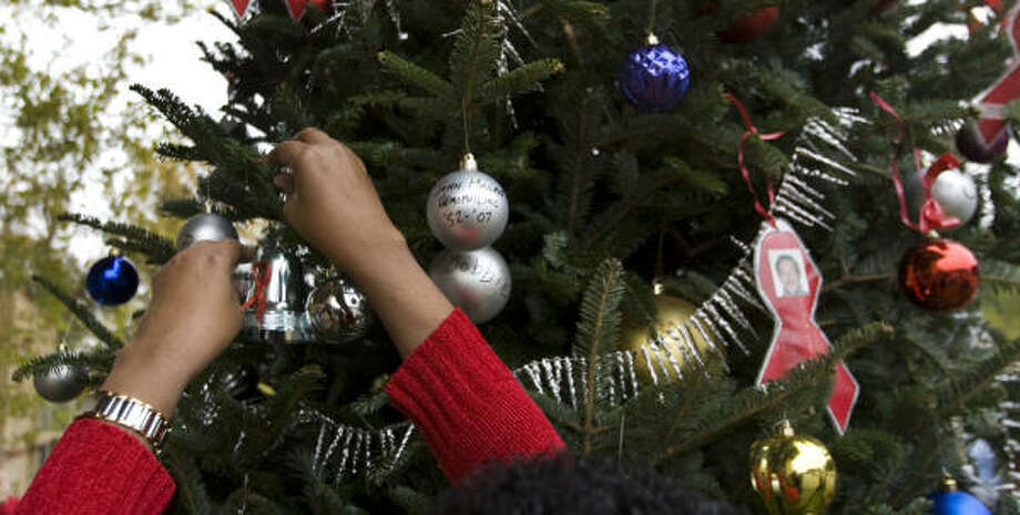 As part of a ceremony marking World AIDS Day, people hang ornaments on a tree at Thomas Street Health Center to honor those lost to HIV and AIDS. Photo: Brett Coomer, Chronicle