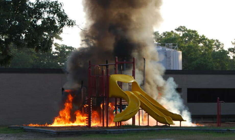 The playground at Fosters Elementary in Kingwood is ablaze moments before Houston firefighters arrive on the morning of July 4. The fire destroyed the playground, which was purchased by the school's PTA in 1998 at a cost of $60,000. Photo: George Brookover, For The Chronicle