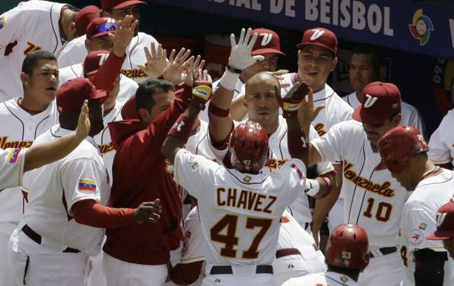 Venezuela's Endy Chavez (47) is congratulated by his teammates after scoring on a groundout by Melvin Mora in the first inning. Photo: Lynne Sladky, AP