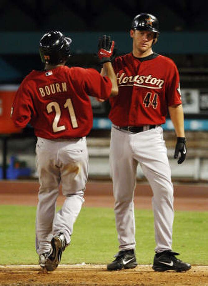 Roy Oswalt (44) congratulates Michael Bourn (21) after both scored on a base hit by Miguel Tejada in the fifth inning. Photo: Alan Diaz, AP