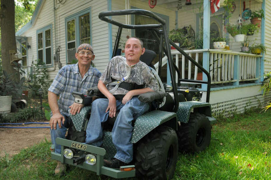"""PRIZE WINNER: Roger Fontaine, 62, left, and his son, Roger, 29, of Splendora, show off the joystick-controlled """"Gecko,"""" an off-road rover invented by the duo that won them recognition by """"Popular Mechanics"""" magazine. The """"Gecko"""" helps Roger Jr., who has muscular dystrophy, get around easier. Photo: Jerry Baker, For The Chronicle"""