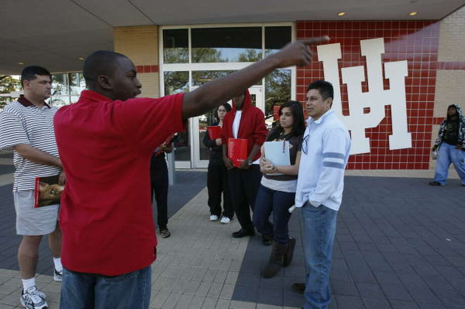 Emmanuel Albert, 19, left, a sophomore with an undecided major, gives a tour to prospective students during a tour of the University of Houston. Photo: Julio Cortez, Chronicle