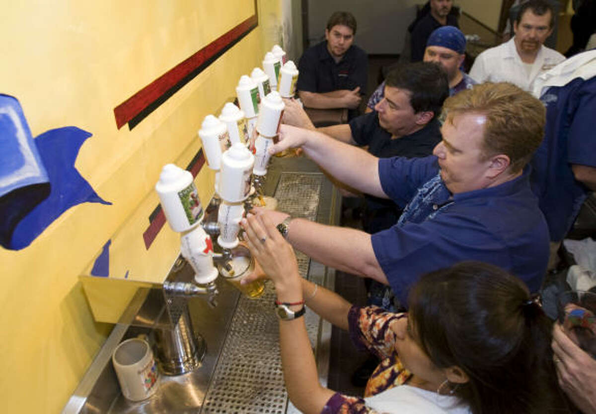 brett coomer : Chronicle FIRST FLOW : Saint Arnold Brewing Company workers pour the first beers from the taps Wednesday during the grand opening party for the company's new brewery outside downtown.