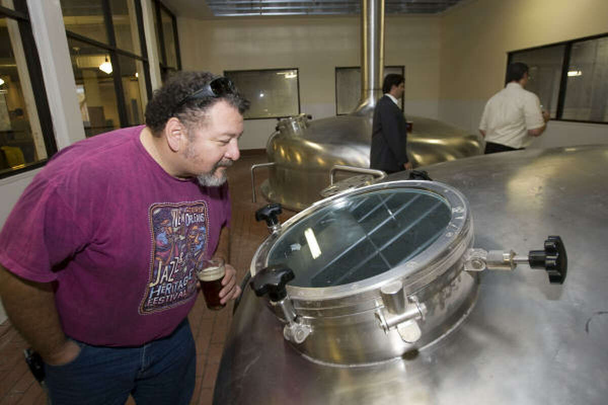 BRETT COOMER : CHRONICLE LOOKING IN: Alex Terronez checks out one of the mash kettles being installed Wednesday during the grand opening party for the Saint Arnold Brewing Company's new facility, The new location, in the 2000 block of Lyons, is at a former HISD warehouse.