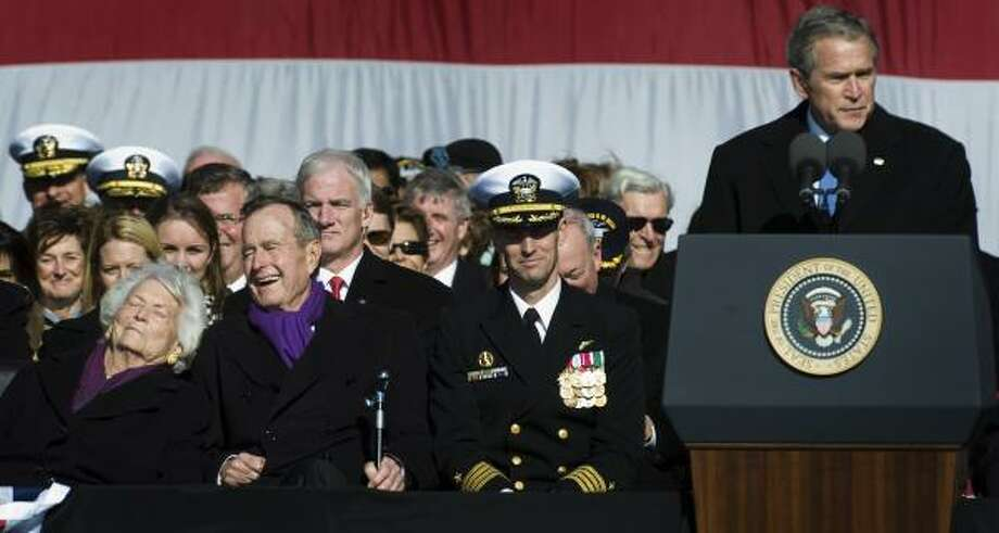 Seated at left, Barbara and George H.W. Bush laugh as their son President George W. Bush jokes during his speech at the ceremony Saturday with Capt. Kevin E. O'Flaherty, center, the ship's commander. Photo: SMILEY N. POOL PHOTOS, CHRONICLE