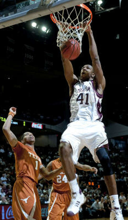 Texas A&M's Chinemelu Elonu dunks over Texas' Gary Johnson during the first half on Monday in College Station. Photo: Wade Barker, AP