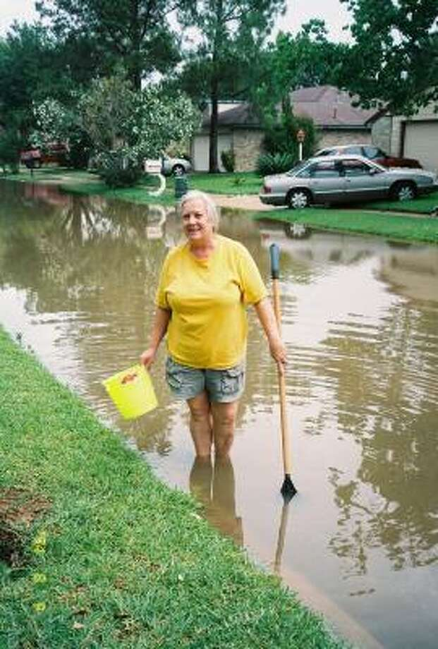 Patricia Harvey, who lives in the 2600 block of Hollymist Drive, was searching for the storm sewer near her home to see if it was blocked, because her street was slower to drain than others along Spanish Needle Drive in the Westlake Place subdivision. Photo: Karen Zurawski, For The Chronicle