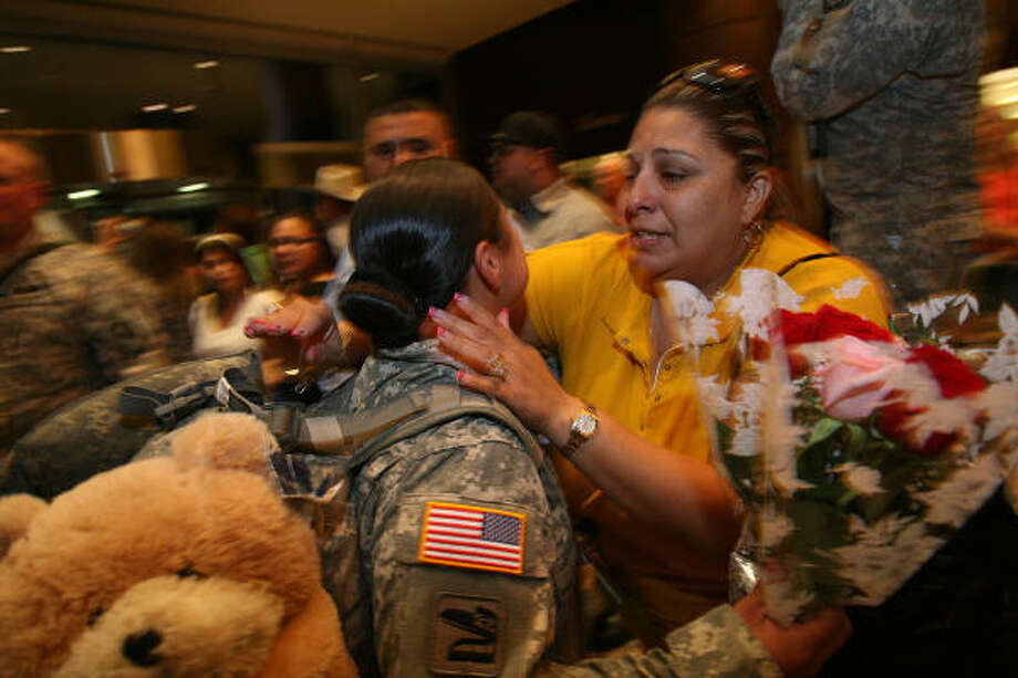 Pfc. Cassandra Mendoza, 19, is embraced by her mother, Veronica Soto, after Mendoza's Baytown-based Texas National Guard unit arrived home after almost a year in Iraq. Photo: Mayra Beltran, Chronicle