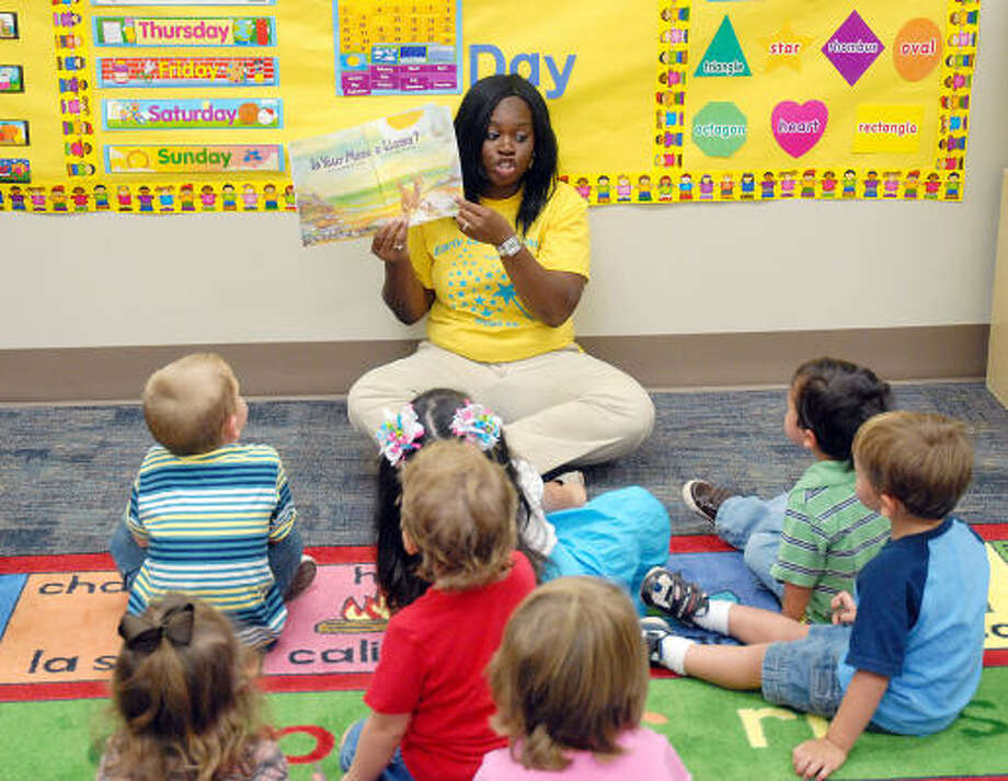 TEACHING TIME: LaToya Akinwoleere reads a story to 3-year-olds at the new Sheldon school district's Early Learning Center on Aug. 13. The learning center is just one of several programs running inside the new Early Childhood Academy. Photo: Dave Rossman, For The Chronicle