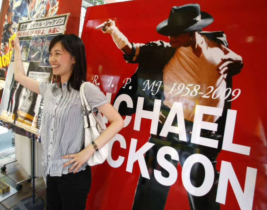 Japanese fan Kiyoko Mori poses in front of a poster of pop legend Michael Jackson at the Tower Records store in downtown Tokyo on Tuesday. Japanese fans gathered at the store for a memorial ahead of the extravaganza set to open later in Los Angeles. Photo: Shizuo Kambayashi, Associated Press