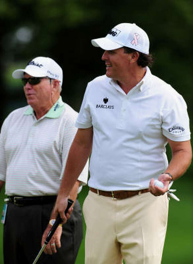 Phil Mickelson, right, plays a practice round Wednesday, with coach Butch Harmon tagging along. Photo: Stuart Franklin, Getty Images