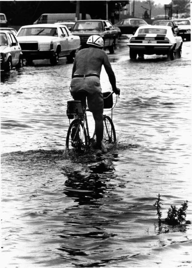 Aug. 8, 1986: A cyclist wearing a helmut but no life jacket pedals through the flooded Shippan Ave. near Magee Ave. in Stamford just after a three hour downpour. A drain that was clogged caused the temporary flooding. Photo: File Photo
