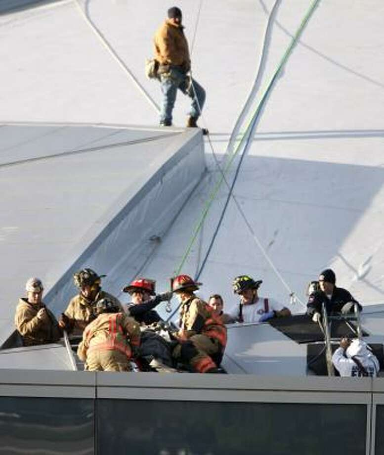 Arlington Fire Department's high angle rescue crew lift an injured worker on a backboard over the lip of the Cowboys Stadium roofline Thursday. Photo: Tom Fox, AP