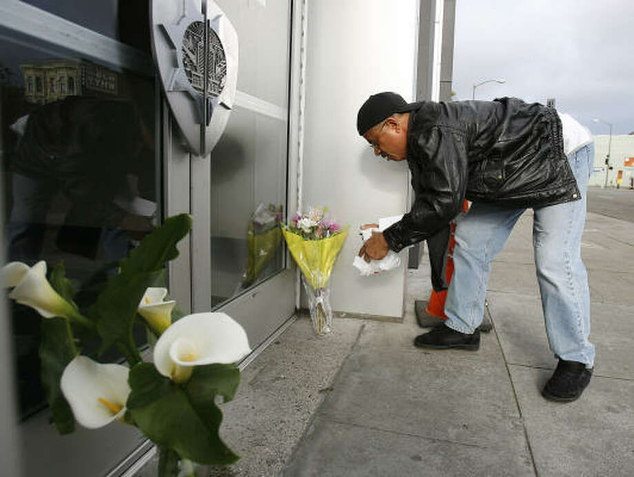 Phillp Long, from Antioch, Calif., leaves flowers at the front entrance of the police station in Oakland on Sunday. Photo: Tony Avelar, AP