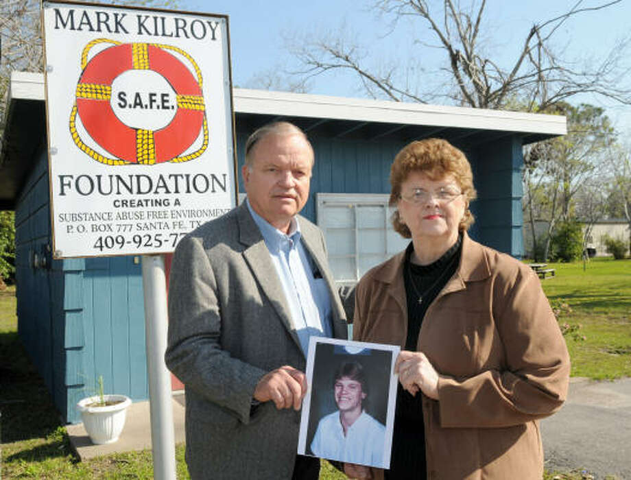 MEMORY LIVES ON: Jim and Helen Kilroy stand outside the Mark Kilroy Foundation's office with a photo of their son, who was abducted and killed by a drug smuggling cult in 1989 while on spring break in Mexico. Photo: Kim Christensen, For The Chronicle