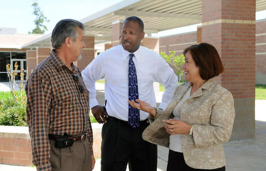 MENTORS UNITE: Waymond Wesley, center, director of the Humble school district's mentoring program, visits with mentors Joe and Rosa Ortega of Kingwood in front of Humble Middle School on April 5. Photo: Jerry Baker, For The Chronicle