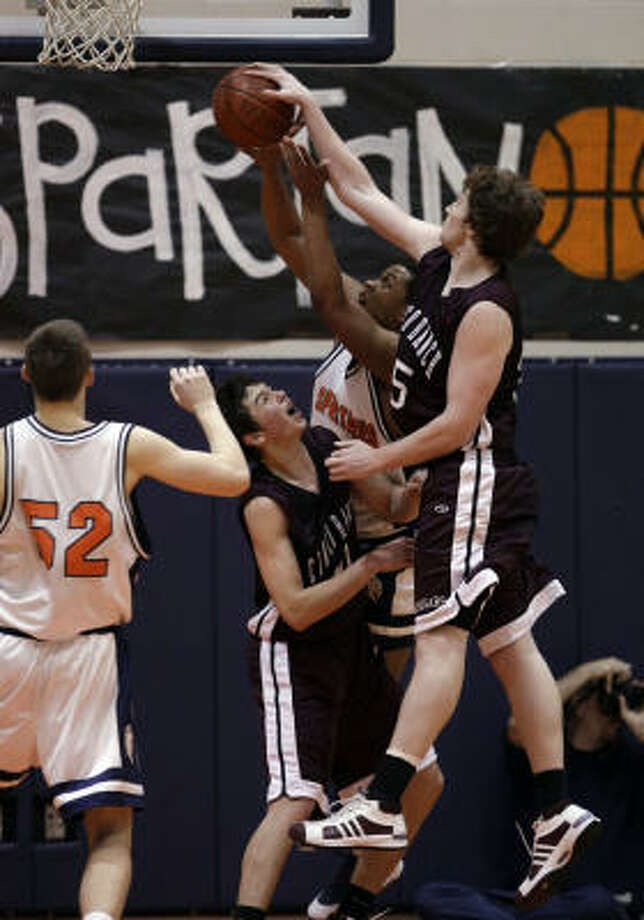 Cinco Ranch's Lewis Butler, right, blocks a shot from Seven Lakes' Jaylon Jones during Tuesday's game. Photo: Bob Levey, For The Chronicle