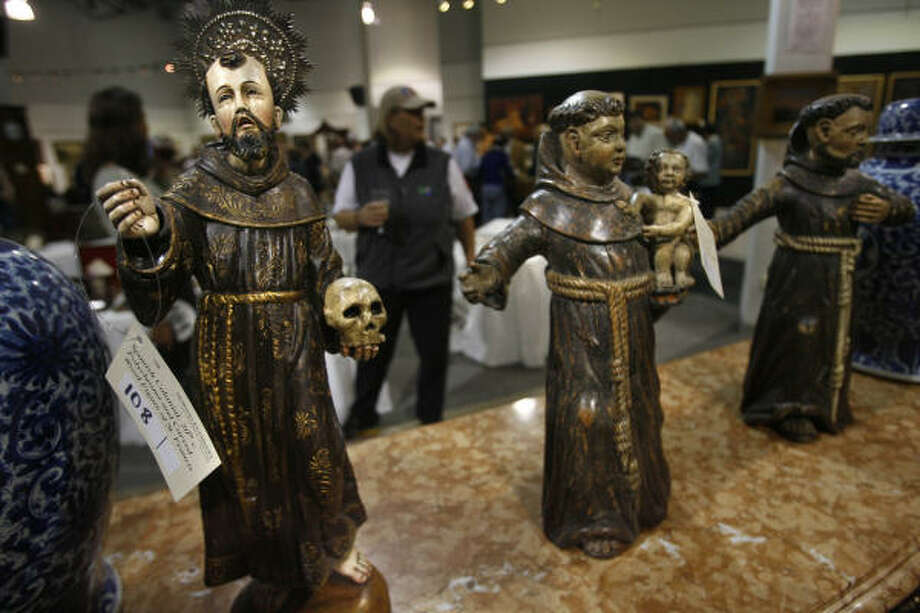 Wood carvings of St. Francis, Spanish Colonial art from the 20th century, are on display before the auction at Kuehnert's Auction Gallery who recently partnered with Mexican auction house Louis Morton, and Thursday was the first auction held since Morton invested in Kuehnert on Feb. 26, 2009 in Houston, TX.  Mayra Beltran / Houston Chronicle Photo: Mayra Beltran, Chronicle