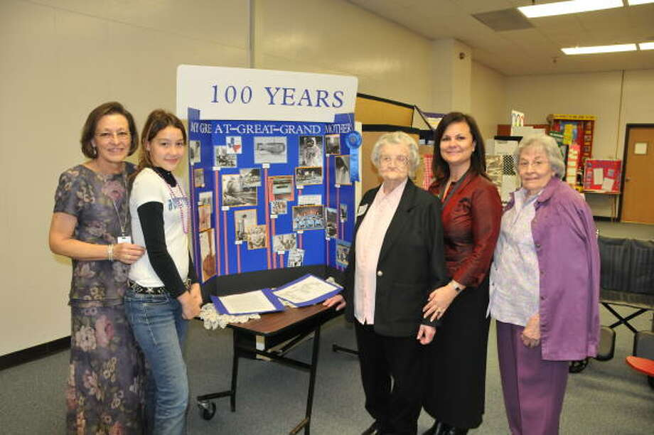 GENERATIONS: Baker Sixth-Grade Campus pupil Chelsey Hoffpauir, second from left, shows her first-place history fair project that she built on the life of her great-great grandmother, Wilma Benita Keener, center, right. With them are Baker social studies teacher Sherry Edwards, left, Baker principal Cynthia Chism, and Chelsey?s great-grandmother, Louise Friday.