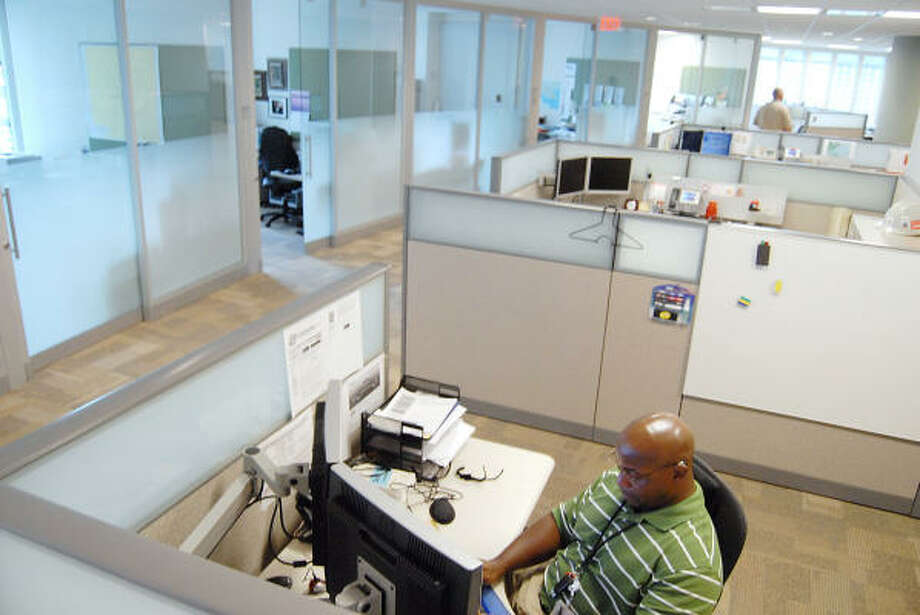 Troy Howard has an open work area, while others at Chevron's Houston tower have walled offices. The energy giant has found that one approach doesn't fit all employees. Photo: DAVE ROSSMAN :, FOR THE CHRONICLE