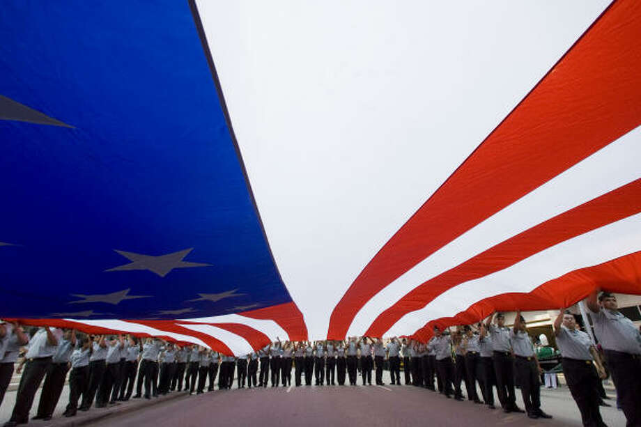 Cadets from the Reagan High School Junior ROTC carry a giant American flag during Wednesday's parade downtown. Photo: James Nielsen, Chronicle