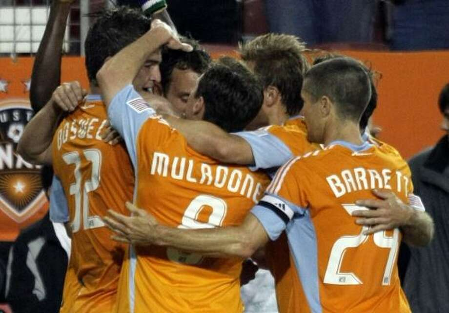Dynamo defender Bobby Boswell, left, is mobbed by teammates Richard Mulrooney, center, and Wade Barrett after scoring during the first half. Photo: Bob Levey, AP