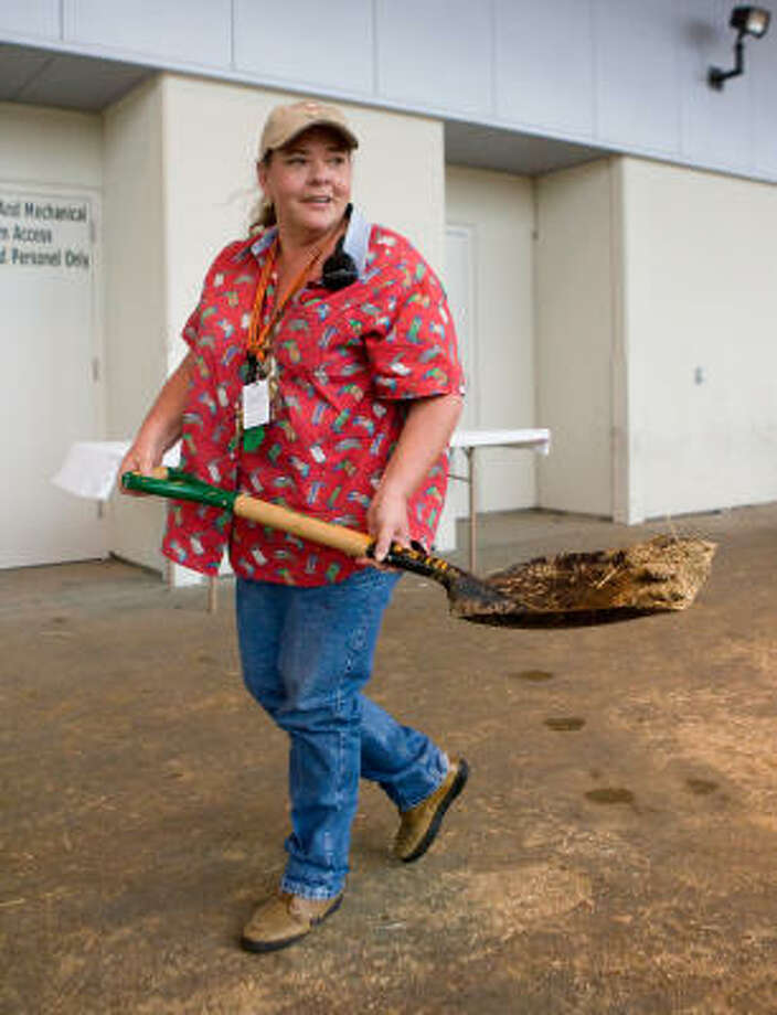 Volunteer Sandra Huebner-Kelly cleans up a mess behind Reliant Center last week.  Photo: Steve Campbell, Houston Chronicle