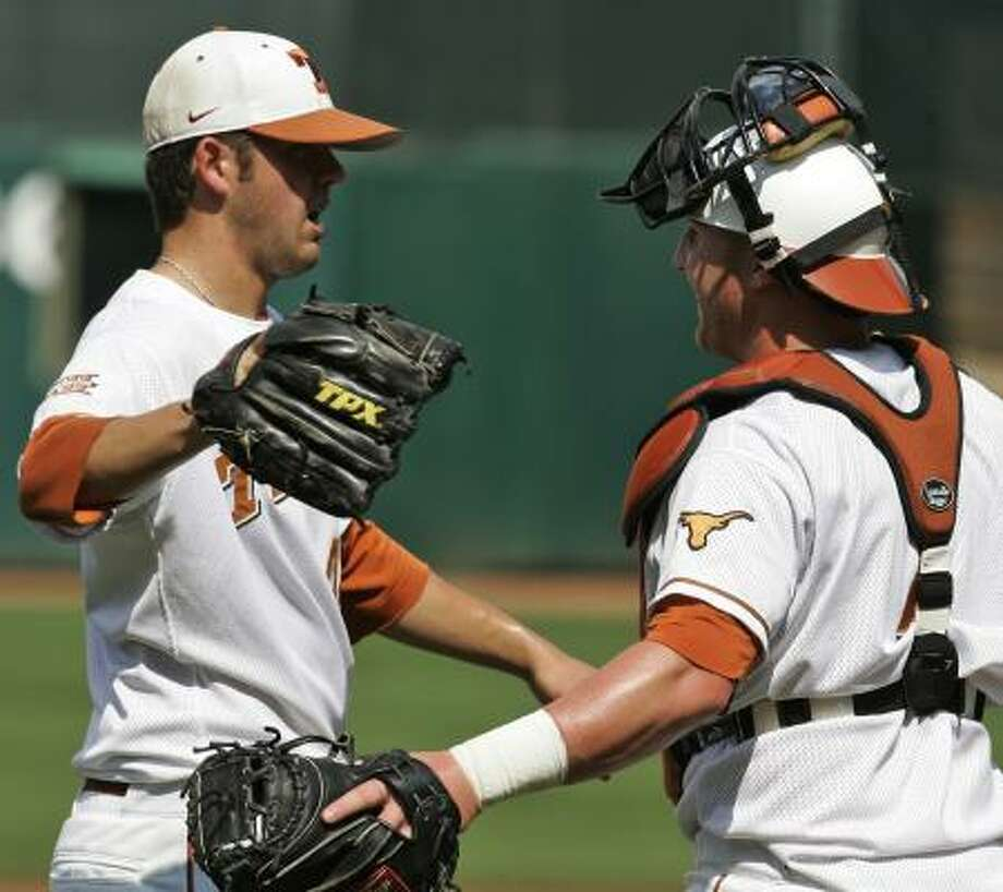 Texas pitcher Austin Wood and catcher Preston Clark celebrate at the end of the game. Photo: AP