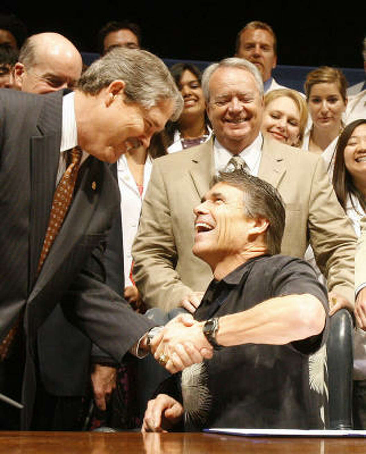 Among measures winning Gov. Rick Perry's approval were House Bills 4586 and 4409. The bills help the University of Texas Medical Branch recover from Hurricane Ike and reform the Texas Windstorm Insurance Association. Perry is shown celebrating with supporters at a bill-signing at UTMB on Friday.