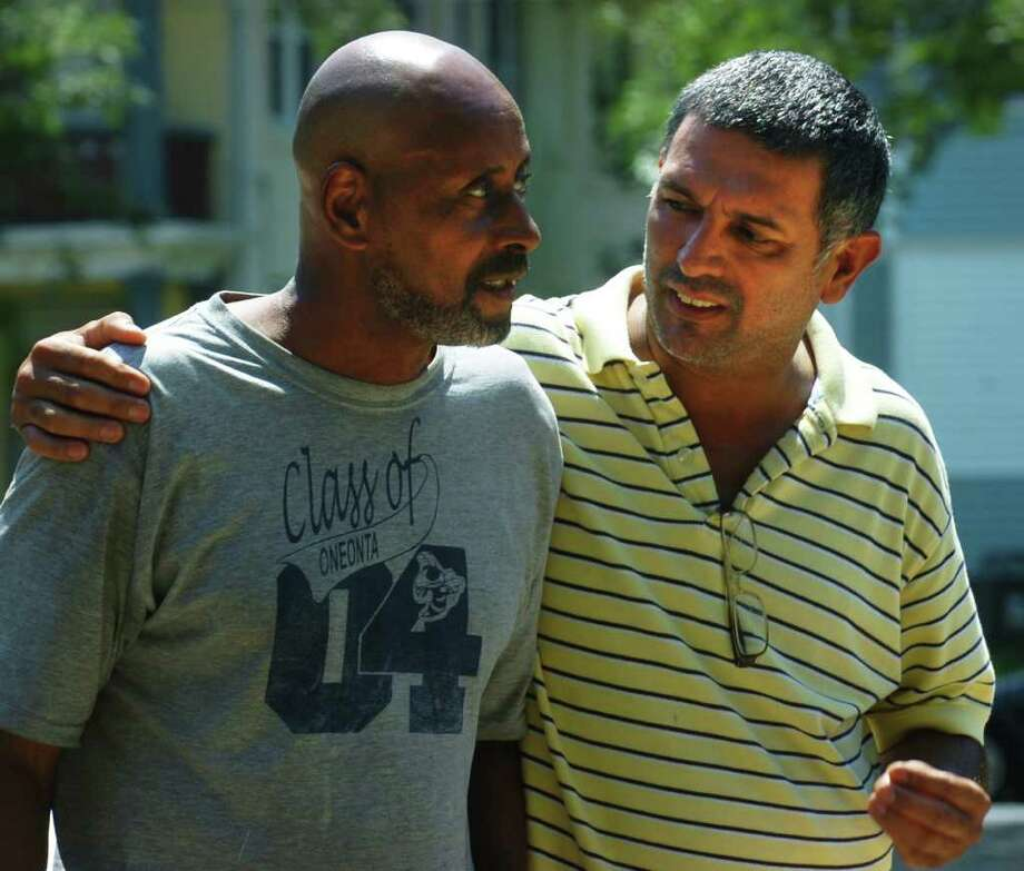 Landlord Pedro Soto, right, speaks with Robert Phillips, one of his tennants who was displaced by an overnight fire at 143 Coleman St. in Bridgeport, Conn. Aug. 5th, 2011. Photo: Ned Gerard / Connecticut Post