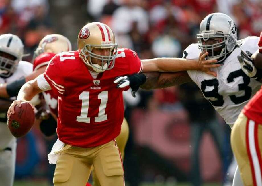 49ers quarterback Alex Smith (11) holds off Raiders defensive end Tommy Kelly (93) in the first quarter during Saturday's 21-20 win against the Oakland Raiders. Photo: Marcio Sanchez, AP