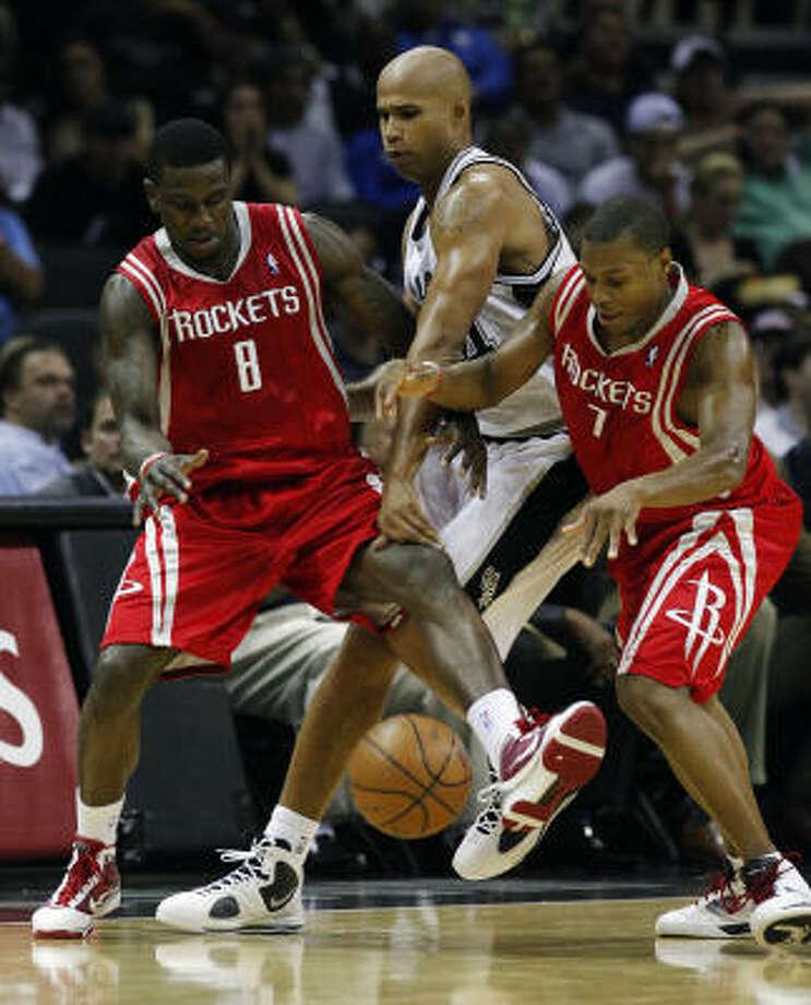 Rockets rookie Jermaine Taylor, left, and Kyle Lowry battle Richard Jefferson for the ball. Photo: Kin Man Hui, San Antonio Express-News