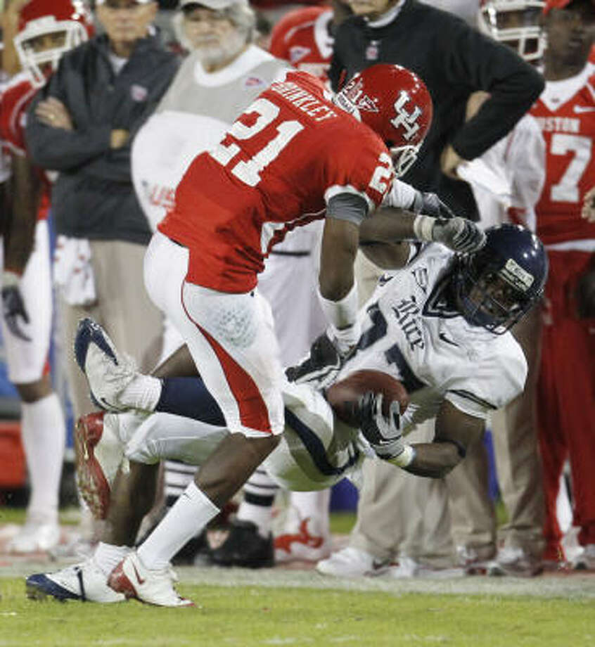 Rice's Tyler Smith, right, finds it impossible to get past Houston's Brandon Brinkley in Saturday's 73-14 rout by UH. Photo: Karen Warren, Chronicle