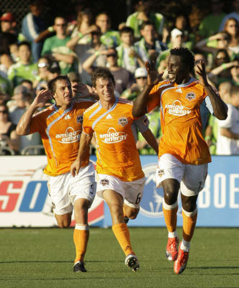 Ade Akinbiyi, right, celebrates his first goal in a Dynamo uniform with Danny Cruz, left, and Erik Ustruck. Photo: Ted S. Warren, AP