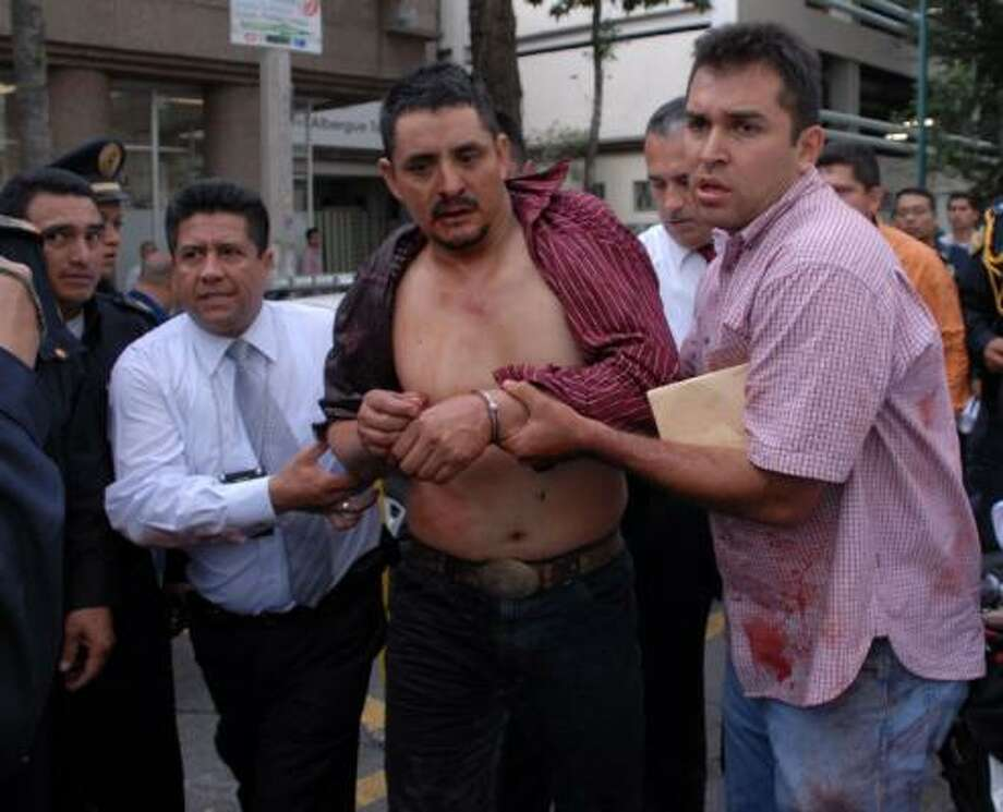 Police arrest the suspected gunman at the site of the shooting at a subway station in Mexico City on Friday. Photo: Associated Press