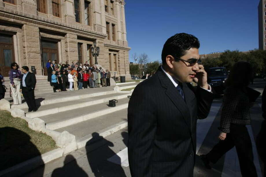 Armando Walle, 30,  gives directions to supporters coming to Austin from Houston for his swearing-in ceremonies Jan. 13. Walle represents District 140. Photo: Julio Cortez, Chronicle