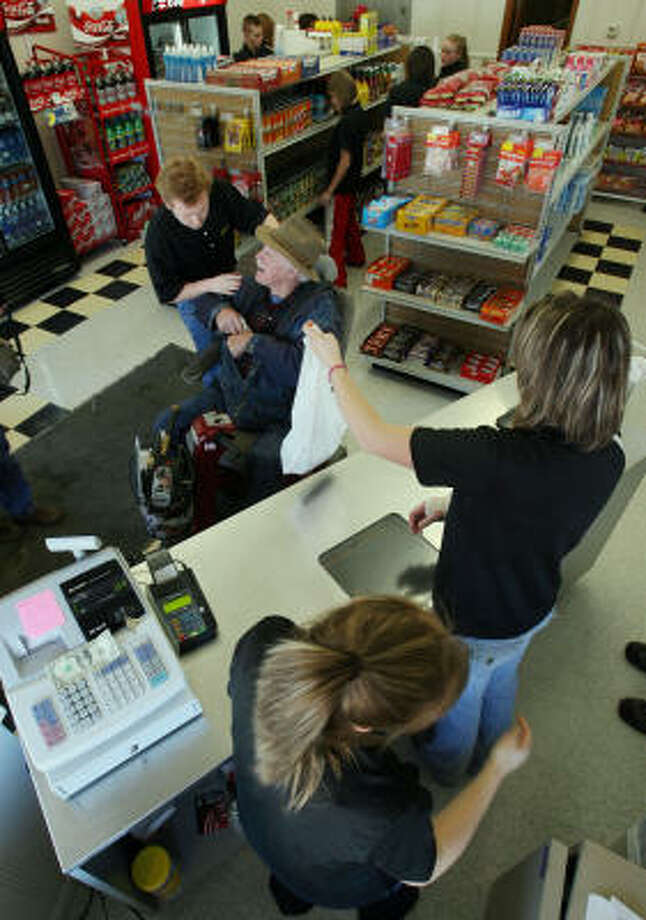 Jim Crowder, in his electric cart, is thanked by teenager Ethan Campbell, who is among a dozen workers in a Leeton, Mo., student-run grocery store that provides services to residents. The next nearest grocery is 15 miles away. Photo: Rich Sugg, MCT