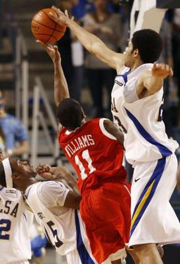 Tulsa's Jerome Jordan blocks the shot of UH's DaShaun Williams as part of a dominating performance Wednesday. Photo: STEPHEN HOLMAN, AP