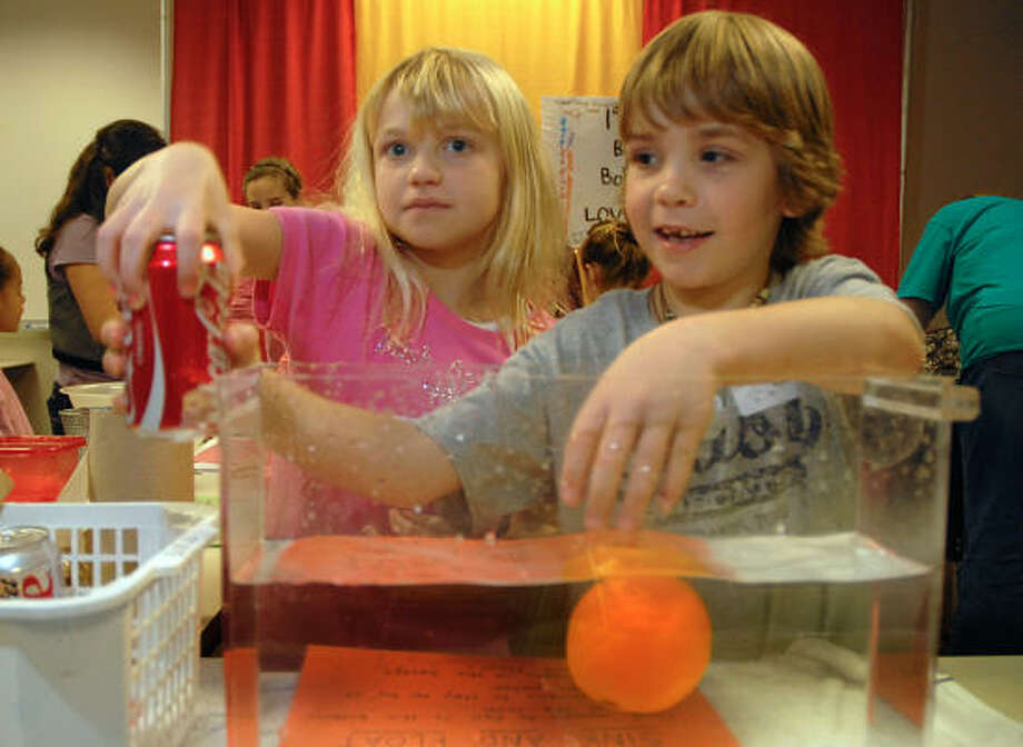 Bush Elementary pupils Madeline Kretschmer and Carsten Ruediger ask guests to choose if an item will sink or float during the SCI://TECH Exposition. Photo: David Hopper, For The Chronicle