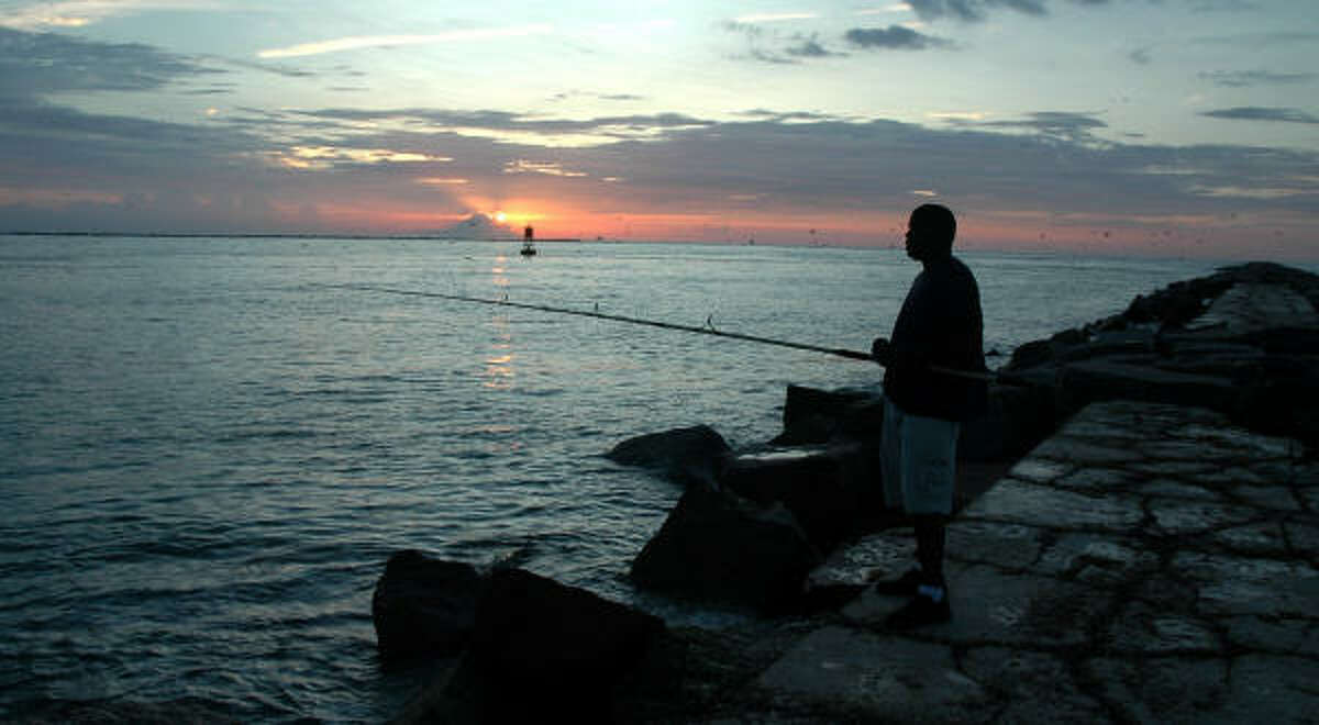 A fisherman waits for something to take his bait in the waters near Port Aransas.
