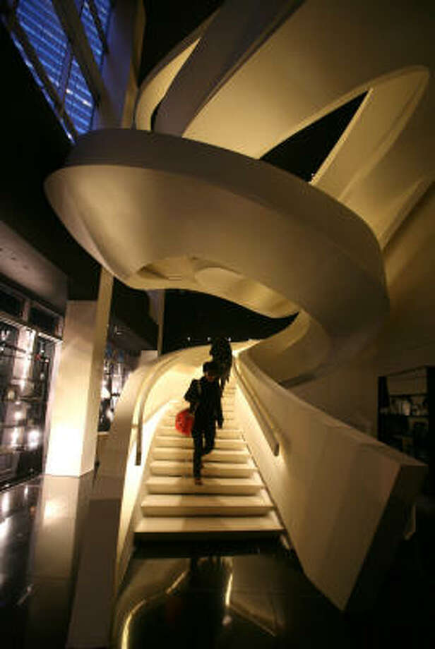 Customers walk down a staircase inside Giorgio Armani's new flagship store in New York. Photo: Diane Bondareff, AP
